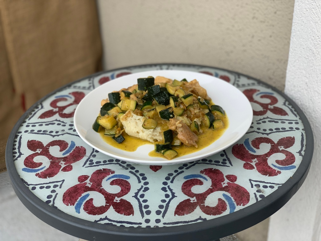 chicken and zucchini dish served over mashed potatoes